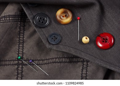 Vintage buttons and pins on black cotton close up