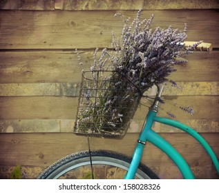 Vintage bycycle with basket with lavender flowers near the wooden wall