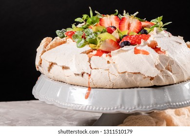 Vintage cake stand with Meringue dessert Pavlova with sugar powder, fresh strawberries, kiwi, blueberries and mint. Copy space.