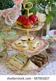 vintage cake stand with scones, sandwiches, strawberry tarts - tea party