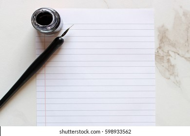 Vintage calligraphy pen and bottle of ink with blank lined paper against white marble desk top with room for copy.