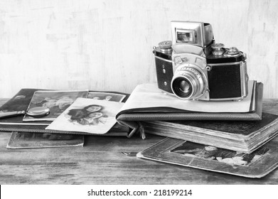 vintage camera, antique photographs and books over wooden table. black and white photo.