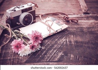 Vintage camera with bouquet of flowers on old wood background - concept of nostalgic and remembrance in spring vintage background