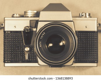 Vintage camera, front view, on light wooden background flat look