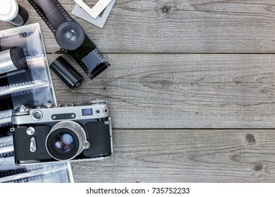 vintage camera and negative films on wooden table  flat view, old memories