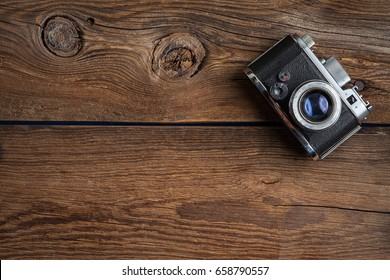 Vintage camera on wooden background. Copy space. Top view.
