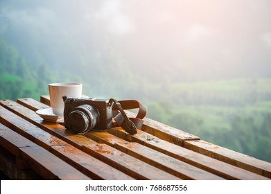 Vintage camera on wooden table and coffee cup in the morning with mountain view background