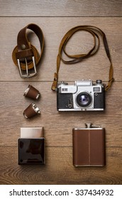 Vintage camera, perfume and leather belt on wooden floor
