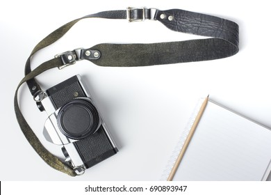 vintage camera with strap and book on white background, top view