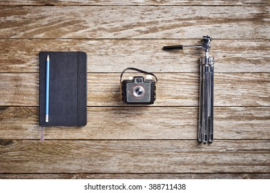 a vintage camera, tripod and journal