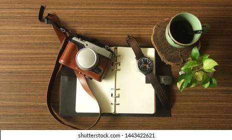 Vintage Camera and Vintage Watch on notebook, Camera and watch on white Blank Book on wooden Table, Warm Tone, Concept Vintage, Style Copy Text Space