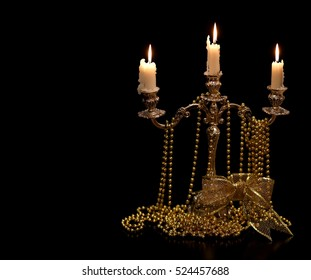 Vintage candlestick with burning candles and Christmas Golden ornaments black background.
