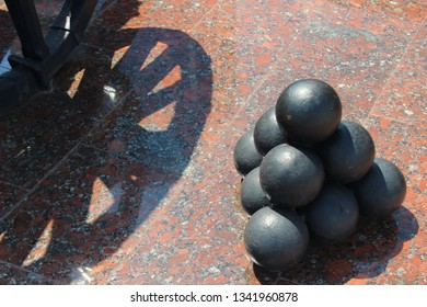 Vintage cannonballs, cannon on wheels, granite background, sunny day