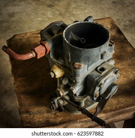 Vintage car carburetor on wood background. Cleaning and fixing carburetor in the garage,butterfly valve seen.
