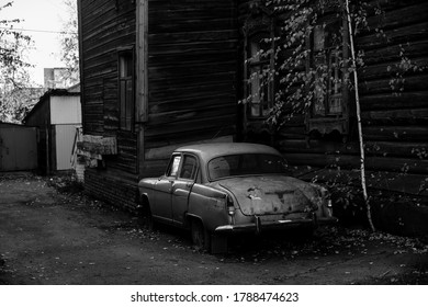 Vintage car near the wooden hause in Tomsk, Siberia. Black and white photo.