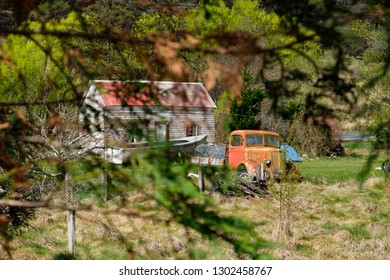 Vintage car next to farmhouse in South Island, New Zealand