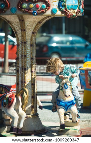 a6c39c9ae Vintage carousel in amusement park. Boy is riding a toy horse in summer park ,