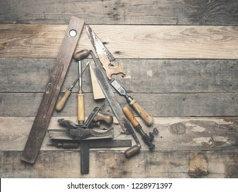 Vintage carpenter tools as a Christmas tree on an old rustic wooden table with space for text on the right