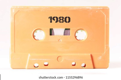 A vintage cassette tape from the 1980s era (obsolete music technology) with the text 1980 printed over it (my addition, not in the original image). Color: cream, sand. White background.