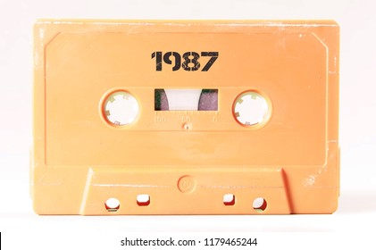 A vintage cassette tape from the 1980s era (obsolete music technology) with the text 1987 printed over it, stencil font. Color: cream, sand. White background.