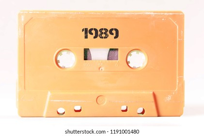 A vintage cassette tape from the 1980s era (obsolete music technology) labeled 1989 (my addition, not in the original image). Color: cream, sand. White background.