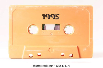 A vintage cassette tape from the 1980s era (obsolete music technology) with the text 1995 printed over it, stencil font. Color: cream, sand. White background.