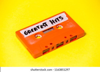 A vintage cassette tape (obsolete music technology), orange on a yellow surface, angled shot, carrying a label with the handwritten text Greatest Hits.