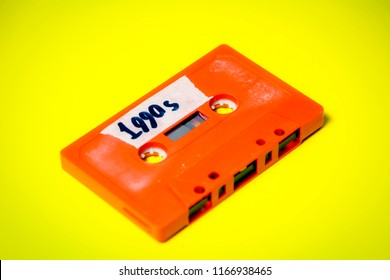 A vintage cassette tape (obsolete music technology), orange on a yellow surface, angled shot, carrying a label with the handwritten text 1990s.