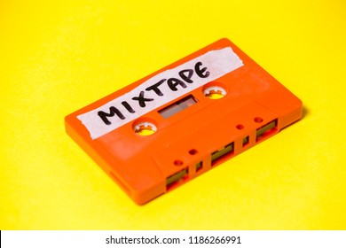 A vintage cassette tape (obsolete music technology), orange on a yellow surface, angled shot, carrying a label with the handwritten text Mixtape.