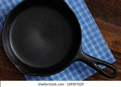 Vintage cast iron skillet with checkered kitchen towel on rustic wood background.  Low key still life with directional, natural lighting for effect.