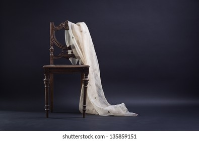 Vintage chair draped with a dark background.