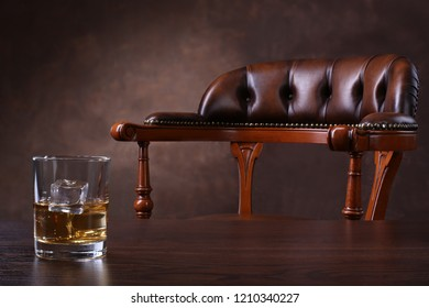 Vintage chair and glass of whiskey on wooden table over brown background
