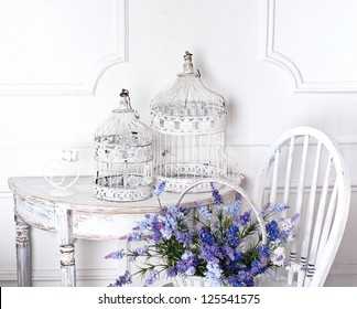 vintage chair and table with flower in front and cages