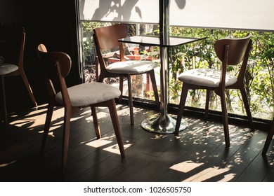 Vintage Chairs and Table near glass window in the coffee shop, Sunlight coming through the window, with Shadow on the wooden floor, with beautiful small garden outside the room. Focus at the table.