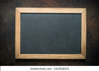 Vintage chalkboard in wooden frame on dark background. Top view copy space.