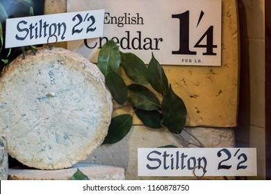 Vintage cheese shop mock-up. Old English stilton and cheddar cheeses display. Traditional British cheeses for sale.Blue veined truckle or cylinder of mature cheese with old world pricing.