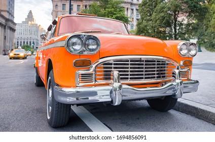 Vintage chequered orange taxi cab in New York City. Manhattan street traffic.