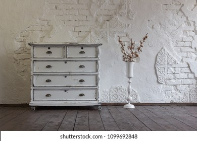 Vintage chest of drawers in the background of the old wall. Vintage interior.