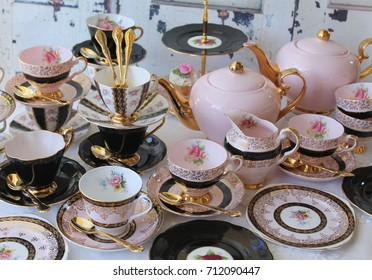 Vintage chic pink and black teacup sets, cake stand, teapots and gold cutlery flatware - high tea party