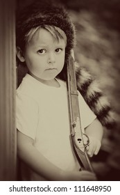 Vintage child with toy rifle and coon skin cap