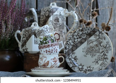 Vintage China, Porcelain Tea Cups on Saucer, Branches with Cones, Heather in Clay, Ceramic Pot, Antique Coffeepot, Sugar Bowl, Plate on Aged Wooden Background, Rustic Style