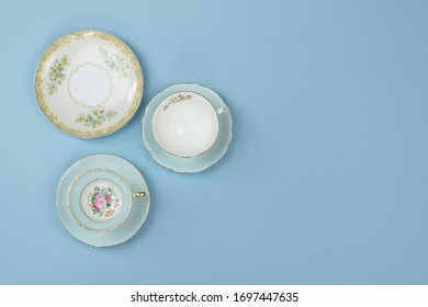 Vintage china teacups on pale blue background with space for copy
