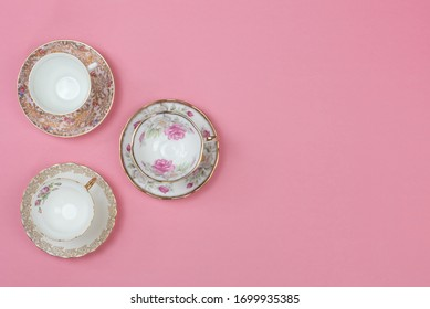 Vintage china teacups on pale pink background with space for copy