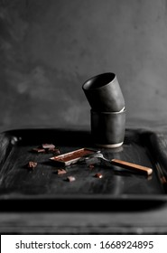 A vintage chocolatebar mold filled with melted dark chocolate and some chocolate chunks and a stack of black coffeecups on a vintage tray against a dark grey background