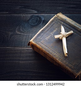Vintage Christian Leather Bible Still Life with Cross made of grass reeds on Dark Wood Board Background.  Square crop photo with drama and above view