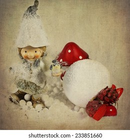 Vintage Christmas background. Cute smiling elf girl, holding a little bird in hand, standing in the snow, near a snowball and red mushrooms.Vintage texture  applied, for a magic fairytale atmosphere