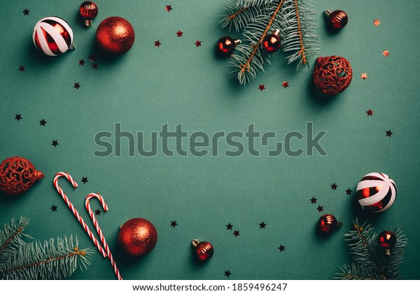 Vintage Christmas background with red and white balls decoration, fir tree branches, candy canes, confetti. Retro Christmas card template.
