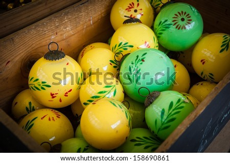 Vintage Christmas balls decorated with flowers and leaves in wooden box. Old times idea. Shadowed angles.