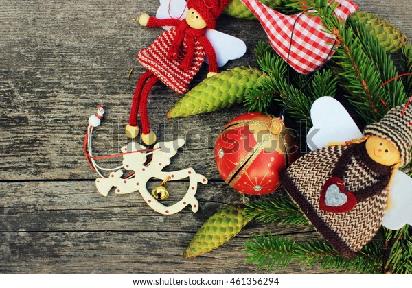 Vintage christmas decor: ball,textile angel, doll and bird with green needles branch on old grey wooden background