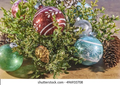 Vintage Christmas old fashioned ornaments still life with boxwood branches on a wooden table with a faded nostalgic feel for a holiday background. Glass ball decorations from the 1950s